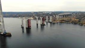 Lucht4k-schot van de bouwwerf van de brug met grote steunen in de rivier stock videobeelden