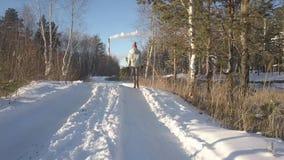 Lucht laag hoek geschoten meisje met pijnboomgangen langs sneeuwspoor stock footage
