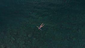 Lucht langzame motie: vrouw die op blauwe waterspiegel drijven, die in transparante Middellandse Zee, top down mening, de zomerva stock footage