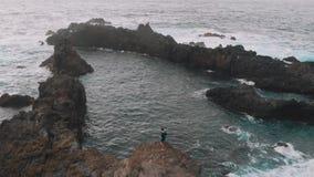 Lucht Mening Een mooie baai in de vorm van een driehoek - de kerel bevindt zich op een klip, naast de natuurlijke pools Tenerife stock videobeelden
