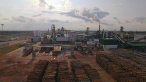 Lucht Mening Houtbewerkingsfabriek De opslag van houtlogboeken, pakhuis De rook komt uit schoorsteen, buis Emissie aan stock videobeelden