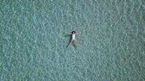 Lucht Mening Mooie jonge vrouw in witte bikini die op waterspiegel in glasheldere turkooise kleurenoceaan drijven stock video