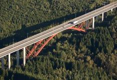 Lucht mening: Rode wegbrug die een bos kruist Royalty-vrije Stock Afbeeldingen