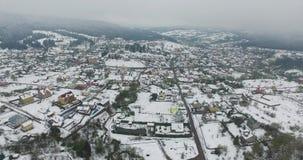 Lucht Mening Sneeuwdorp in de vallei van de bergen stock footage