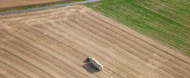 Lucht Mening: Tractor die op gebieden werkt stock foto