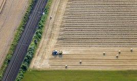 Lucht Mening: Tractor op een gebied langs een spoorweg royalty-vrije stock foto