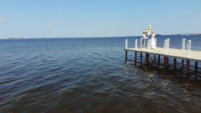Lucht video, mooie jonggehuwdepaar, bruid en bruidegom die, op een mooie pijler, tegen het blauwe overzees in openlucht dansen en stock videobeelden