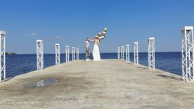 Lucht video, mooie jonggehuwdepaar, bruid en bruidegom die, op een mooie pijler, tegen het blauwe overzees in openlucht dansen en stock video