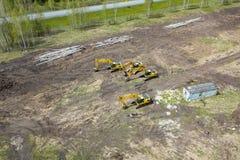 Lucht zijaanzicht van vier gele kruippakjegraafwerktuigen die zich op grond dichtbij de bouwwerf bevinden en op de werkdag wachte royalty-vrije stock fotografie