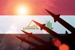 Luchtafweerrakettensilhouetten op achtergrond van de vlag van Irak Stock Afbeelding