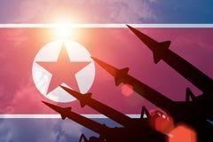 Luchtafweerrakettensilhouetten op achtergrond van de vlag van Noord-Korea Stock Fotografie