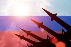 Luchtafweerrakettensilhouetten op achtergrond van de vlag van Rusland Stock Foto