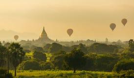 Luchtballons over Boeddhistische tempels bij zonsopgang in Bagan Stock Afbeeldingen