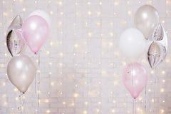 Luchtballons over witte bakstenen muurachtergrond met lichten royalty-vrije stock foto's