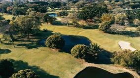 luchtbeeld van een golfgebied en een park met sommige zand en waterpools met mooi gras en de stad zichtbaar op de achtergrond stock fotografie