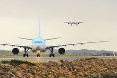 Luchtbus A330 op baan met tweede vliegtuig die erachter landen Royalty-vrije Stock Foto