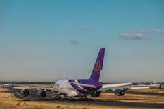 Luchtbus A380 van Thaise luchtroutes die zich op taxibaan door slepenvrachtwagen bewegen stock fotografie