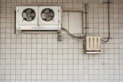 Luchtcompressor op de uitstekende bakstenen muur stock fotografie