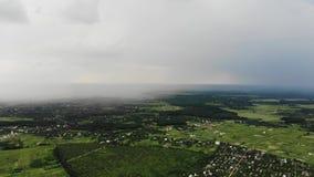 Luchtdiehommel van zware regenval wordt geschoten die het dorp in de voorsteden naderen stock footage