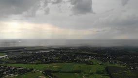 Luchtdiehommel van zware regenval wordt geschoten die het dorp naderen stock footage