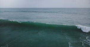 Luchtdiehommelluchtparade van grote oceaangolf wordt geschoten die met wit schuim in adembenemende donkerblauwe open oceaan en ho stock videobeelden