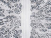 Luchtdiehommelmening van de winterbos en weg met sneeuw wordt behandeld royalty-vrije stock afbeelding