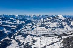 Luchtdiehommelmening van vallei in sneeuw binnen - tussen bergen wordt behandeld stock afbeeldingen