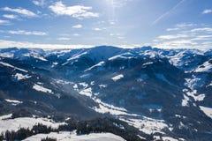 Luchtdiehommelmening van vallei in sneeuw binnen - tussen bergen wordt behandeld royalty-vrije stock afbeeldingen