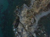 Luchtfotografie van de kust van Sardinige tijdens een de zomerzonsondergang Kleine die golven op de rotsen met een hommel worden  royalty-vrije stock afbeelding