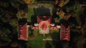 LUCHTgezoem uit Kasteel Vlucht over mooi kasteel; gevestigd in landschapspark met groene bomenbossen in de herfst 4K stock footage