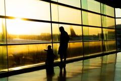 Luchthaven, familie die op hun vlucht, silhouet wacht van vader met jonge geitjes, Dublin Ireland royalty-vrije stock fotografie