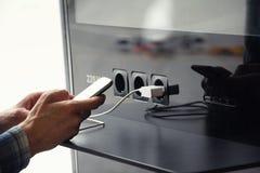 Luchthaven openbare lader en man handen met smartphone Vliegtuig royalty-vrije stock fotografie