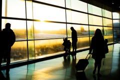 Luchthaven, silhouet van vader met jonge geitjes en passagiers, Dublin Ireland, zonsopgang royalty-vrije stock foto's