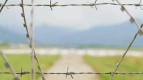 Luchthavenmening door de prikkeldraadomheining in bergen - Georgië stock footage