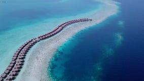 Luchthommel die rij van strawy bungalowwen langs strand schieten stock footage