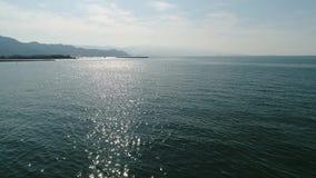 Luchthommel die, terugtocht binnen van kalme, blauwe sea  vliegen stock videobeelden