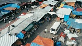 luchthommelbeeld van de markt van de ochtendstad met kleurrijke tenten die onderaan close-up kijken terwijl mensen die rondwandel stock afbeelding