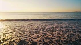 Luchthommellengte van overzeese golven die strand bereiken tijdens zonsondergang stock video