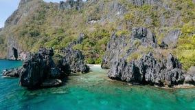 Luchthommelmening over een tropisch koraalrif en een rotsachtig vormingen Verborgen Strand, het Nationale Park van Gr Nido Palawa stock videobeelden