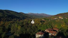 Luchthommelmening over kerk in Bulgaars dorp in de berg Kopren, Bulgarije stock video
