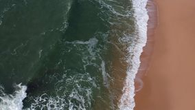 Luchthommelmening van blauwe oceaangolven die op het zand van een gouden strand in Portugal breken stock video