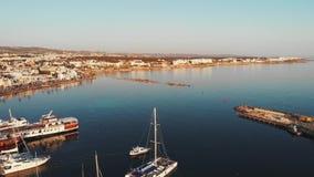 Luchthommelmening van de haven van de stadsjachthaven met boot die aan het overzees met stad en bergen op achtergrond varen Jacht stock footage