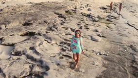 Luchthommelmening van gezonde jonge vrouw in kleding en zonnebril die op tropisch strand dichtbij oceaan tijdens mooi lopen stock videobeelden