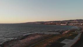Luchthommelmening van Middellandse Zee met golven op zonsondergang met stad en bergen op achtergrond Kust met voetweg stock video