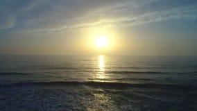 Luchthommelmening van mooie zonsopgang over het zeewater en het strand stock videobeelden