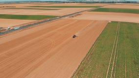 Luchthommelmening van rode tracor die op tarwegebied werken Landbouw en milieu in Europese Unie stock footage