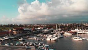 Luchthommelmening van stadshaven met veel jachten en boten Hommelschot van eiland met stadshaven en toeristenpromenade bij zon stock footage