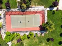 Luchthommelmening van Tennisbaan in de Tuin met Spelers die Tennis spelen royalty-vrije stock foto's