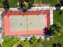 Luchthommelmening van Tennisbaan in de Tuin met Spelers die Tennis spelen stock fotografie