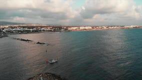 Luchthommelmening van weinig witte vissersbootzeilen uit van mooie stadshaven in open zee bij zonsondergang stock footage